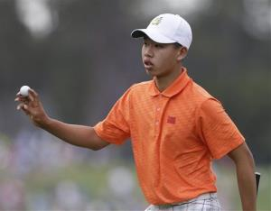 Amateur Guan Tianlang of China hold up his ball after putting on the first green.