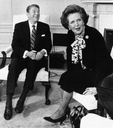 In this Feb. 20, 1985 file photo, Margaret Thatcher turns to look at the crush of photographers in the Oval Office as President Reagan laughs during a photo session at the White House in Washington.