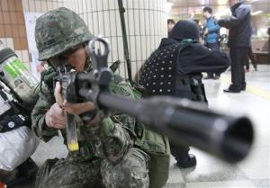 A South Korean army soldier aims his machine gun during an anti-terrorism drill at a subway station in Seoul today.