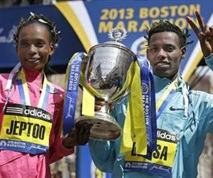 Rita Jeptoo of Kenya and Lelisa Desisa of Ethiopia pose with a trophy at the finish line after winning the women's and men's divisions of the 2013 Boston Marathon in Boston, April 15, 2013.