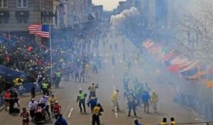 People react as an explosion goes off near the finish line of the 2013 Boston Marathon in Boston, Monday, April 15, 2013.