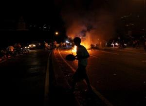 An opposition supporter bangs during a protest in Caracas, Venezuela, last night.