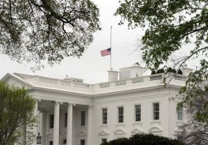 The American flag is lowered at the White House Tuesday to honor the victims in Boston.