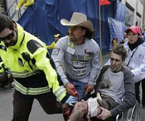 An emergency responder and volunteers, including Carlos Arredondo in the cowboy hat, push Jeff Bauman in a wheelchair after he was injured at the Boston Marathon Monday, April 15, 2013 in Boston.
