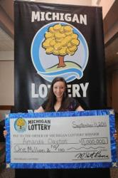 Amanda Clayton holds her ceremonial $1 million lottery check. Clayton was found dead of a possible drug overdose. She had been charged with fraud after continuing to receive $5,400 in public benefits.