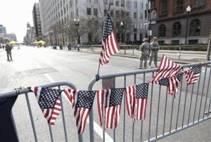 US flags hang from a barricade as Massachusetts National Guard members keep watch of Boylston Street near the Boston Marathon bomb site, April 16, 2013.