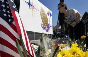 Shannon Walsh, 15, places flowers on a memorial to Boston Marathon bombing victim, Martin Richard, 8, near the Richard family house in the Dorchester neighborhood of Boston, Wednesday, April 17, 2013.