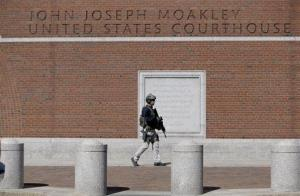An official wearing tactical gear stands guard outside the  federal courthouse in Boston Wednesday.