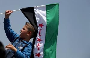 A boy waves the Syrian revolutionary flag as protesters chant anti-Bashar Assad slogans in front of the Syrian embassy, in Amman, Jordan, Friday, April 12, 2013.