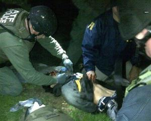ATF and FBI agents check suspect Dzhokhar Tsarnaev for explosives and  give him medical attention after he was apprehended in Watertown, Mass.