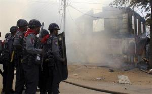 In this Thursday, March 21, 2013 file photo, armed Myanmar police officers provide security around a smoldering building following ethnic unrest between Buddhists and Muslims.
