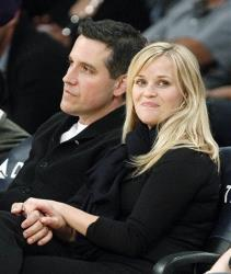 Reese Witherspoon and her husband Jim Toth watch the Toronto Raptors take on the Los Angeles Lakers in an NBA basketball game in Los Angeles Friday, March 8, 2013.
