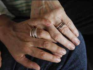 In this July 20, 2012, photo, Carol Anastosio and Mimi Brown, who were among the first couple to wed under New York's gay marriage law, hold hands showing wedding bands made by a friend.
