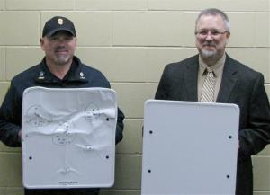 In this April 22 photo provided by the Cold Spring Record, Cold Spring Police Chief Phil Jones, left, and Rocori School District Superintendent Scott Staska pose with bulletproof whiteboards.
