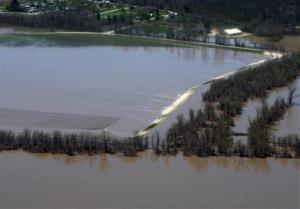This Saturday, April 20, 2013, photo, provided by the Missouri Department of Public Safety shows an overtopped levee north of Clarksville, Mo. and the flood wall protecting the city.