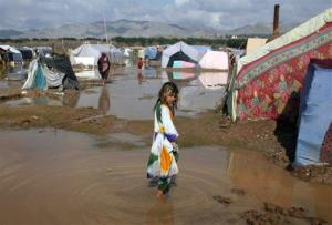 An internally displaced girl walks in flood waters at a refugee camp in Herat, west of Kabul, Afghanistan, Feb. 3, 2013.