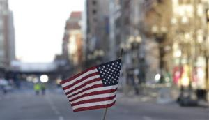 A flag sits on a barricade on Boylston Street near the finish line of the Boston Marathon, Wednesday, April 17, 2013, in Boston.