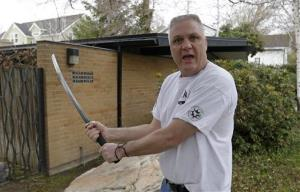 Kent Hendrix, 47, draws his sword near his house Tuesday, April 23, 2013, in Salt Lake City.