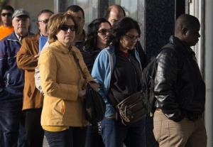 People enter an office to register for job placement in Madrid, Spain, Thursday, April 25, 2013.