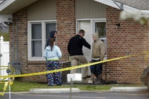 Police officials investigate the scene at a house in Manchester, Ill., where five people were found slain in the tiny southwestern Illinois town early yesterday.