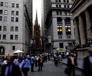 With Trinity Church in the background, people walk on Wall Street, Monday, Sept. 29, 2008 in New York.