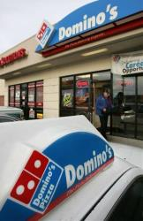In this Feb. 11, 2007 file photo, a Domino's Pizza delivery driver heads to his car with orders in Sandy, Utah.