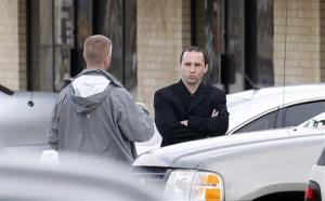 Everett Dutschke, right, confers with a federal agent Wednesday near the site of a martial arts studio he once operated in Tupelo, Miss.