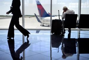 A passenger sits at right in the international terminal at Hartsfield-Jackson airport Friday in Atlanta.