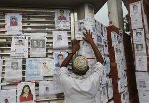 A Bangladeshi puts up a picture of his missing relative at a makeshift morgue in a schoolyard near a building that collapsed Wednesday in Savar, near Dhaka, Bangladesh, Saturday, April 27, 2013.