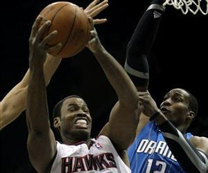Then-Atlanta Hawks center Jason Collins (34) goes up for a shot against Orlando Magic center Dwight Howard (12) during the first quarter of an NBA Basketball game Monday, Dec. 20, 2010, in Atlanta.