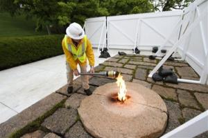 This handout photo provided by Arlington National Cemetery shows an engineering technician lighting a torch from JFK's eternal flame. A temporary flame will burn while the regular one gets an upgrade.