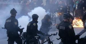 Protesters react as a police flash-bang grenade goes off during a May Day march, May 1, 2013, in downtown Seattle.