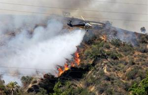 A Los Angeles County Fire Department helicopter dropping water on a fire burning on the foothills of the San Gabriel Mountains in Monrovia, California.