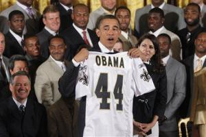 President Barack Obama holds up a personalized New Orleans Saints team jersey.