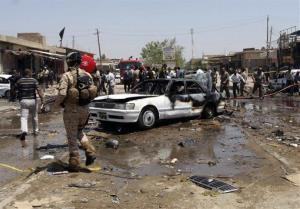 Civilians and security forces gather at the scene of a car bomb attack in the southern Shiite city of Karbala on April 29.