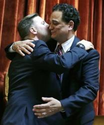 Rhode Island House Speaker Gordon Fox, right, embraces his partner Marcus LaFond after today's vote in Providence.