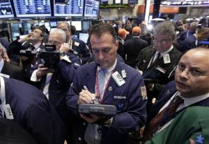 In this May 2 photo, traders gather at a post on the floor of the New York Stock Exchange.
