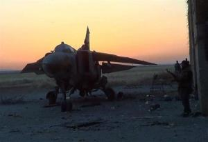 This citizen journalism image provided by the Syrian Revolution Against Bashar Assad shows Syrian rebels, right, standing next a damaged warplane, at Abu Dhour military airbase in Idlib, Syria.