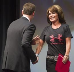 NRA official Chris W. Cox greets Sarah Palin (in a Women Hunt T-shirt).