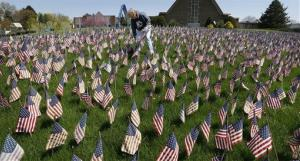 Nancy Nogacek helps tend to American flags on display in front of Memorial Park Church in McCandless, Pa. The display commemorates veterans killed in Iraq and Afghanistan.