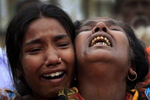 A woman is comforted as she grieves after identifying the body of her daughter, a victim of the garment factory collapse, Sunday, May 5, 2013 in Savar, near Dhaka, Bangladesh.