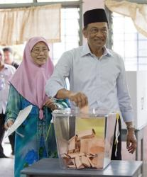 Malaysian opposition leader Anwar Ibrahim votes with his wife Wan Azizah at a polling station at Penanti in Penang state in northern Malaysia, Sunday, May 5, 2013. Malaysian's go to the polls Sundy in what could be the toughest test of the ruling coalition's 56-year grip on power in Southeast...