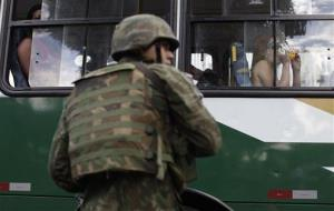 A soldier stands by a bus during a police operation in Rio de Janeiro, Brazil.