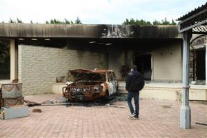 A man walks near a charred vehicle at the entrance of the damaged American consulate building in Benghazi, Libya.