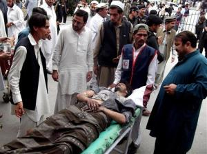 People stand near a man injured from the blast in the Pakistani tribal area of Parachinar yesterday.