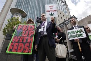 Medical marijuana demonstrators hold up signs outside of the Federal Courthouse in Sacramento, Calif. yesterday.
