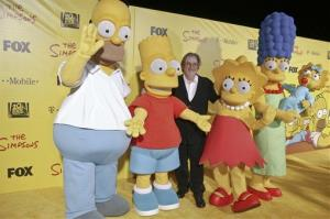 Matt Groening, center, is flanked by people costumed as, from left, Homer Simpson, Bart Simpson, Lisa Simpson, and Marge Simpson holding Maggie Simpson.
