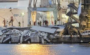 Rescuers search what is left of the control tower of the port of Genoa, northern Italy.