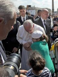 Pope Francis is hugged by a young girl with whom he exchanged skull caps after stepping out of his pope-mobile to walk the last part of his way to the altar, to deliver his weekly general audience in St. Peter's Square at the Vatican, Wednesday, May, 8, 2013.