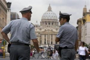 Italian financial Police officers talk to each other with St. Peter's Basilica at the Vatican in the background.
